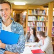 Male student with others in background at library — Stock Photo #36246539