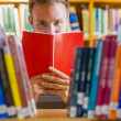 Stock Photo: Male student selecting book in library