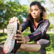 Pretty sporty woman stretching her leg in park — Stock fotografie