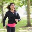Beautiful healthy young woman jogging in the park — Stock Photo