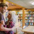 Young romantic couple with bookshelf at distance in library — Stock Photo #36246917