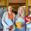 Students reading book against bookshelf in library — Stock Photo