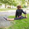 Stock Photo: Flexible young womdoing splits exercise in park