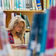 Smiling female student reading book in the library — Stock Photo #36247119