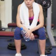 Tired and thoughtful young woman sitting in gym — Stock Photo