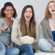 Cheerful friends with remote control and popcorn bowl on sofa — Stock Photo