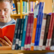 Male student selecting book in the library — Stock Photo #36247285