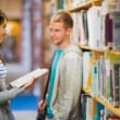 Two young students selecting a book in the library — Stock Photo #36247525