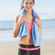 Beautiful healthy woman with towel around neck on beach — Stock Photo