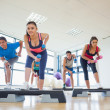 Instructor with fitness class performing step aerobics exercise with dumbbells — Stock Photo #36247881