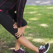 Mid section of woman stretching her leg during exercise at park — Stock Photo