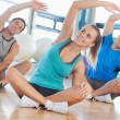 Fitness class and instructor sitting and stretching hands — Stock Photo