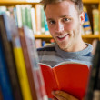 Male student selecting book in the library — Stock Photo #36248553