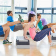 Instructor with fitness class performing step aerobics exercise — Stock Photo