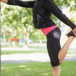 Side view of a woman stretching her leg during exercise at park — ストック写真