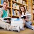 Students reading books on the library floor — Stock Photo