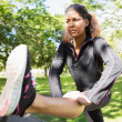 Sporty woman stretching her leg while standing in park — Stock Photo #36249667