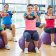 Fitness class sitting with dumbbells on exercise balls — Stock Photo #36249673