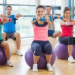 Fitness class sitting with dumbbells on exercise balls — Stock Photo
