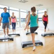 Instructor with fitness class performing step aerobics exercise — Stock Photo #36249769