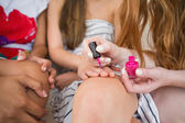 Mid section of a young woman painting friend's nails — Stock Photo