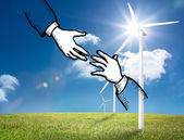 Two hands graphic on bright countryside with wind turbines — Stock Photo