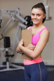 Entrenador femenino sonriente con portapapeles en gimnasio — Foto de Stock