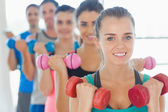People lifting dumbbell weights with trainer in gym — Stock fotografie