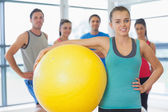 Instructor holding exercise ball with fitness class in background — ストック写真