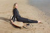 Portrait of a blond in wet suit with surfboard at beach — Stock Photo