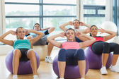 Class doing abdominal crunches on fitness balls — Stock Photo