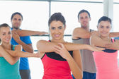 Portrait of sporty people stretching hands at yoga class — Stock Photo