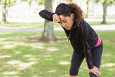 Tired woman taking a break while jogging in park — Stock Photo