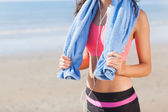 Mid section of healthy woman with towel around neck on beach — Stock Photo