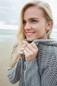 Cute smiling woman in gray knitted jacket on beach — Стоковое фото