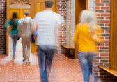 Blurred students walking through corridor — Stock Photo