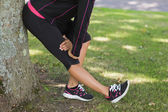 Low section of woman stretching her leg during exercise at park — Stock Photo