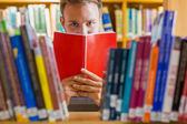 Male student selecting book in the library — Stock Photo