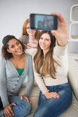 Happy friends photographing themselves with smartphone — Stock Photo