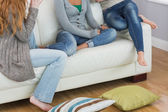 Friends sitting on sofa with cushion on floor at home — Stock Photo
