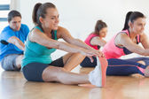 Class and instructor stretching legs in exercise room — ストック写真