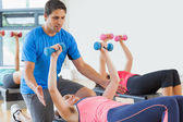 Trainer helping woman at fitness studio — Stock Photo