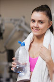 Portrait of a smiling woman with water bottle in gym — Stock Photo