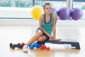 Young woman sitting with dumbbells in fitness studio — Stock Photo