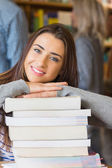 Student with stack of books while others in background at library — Stock Photo
