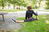 Flexible young woman doing the splits exercise in park — Stock Photo