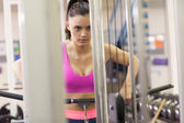 Determined woman doing exercises in gym on lat machine — Stock Photo