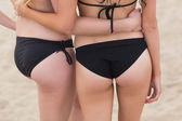 Mid section of two young bikini women at the beach — Stockfoto