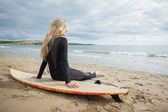 Smiling beautiful blond in wet suit with surfboard at beach — Stock Photo