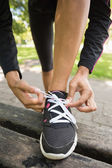 Close up low section of sporty woman wearing shoes in park — Stock Photo